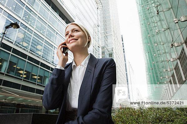 Geschäftsfrau auf Handy unter Bürogebäude