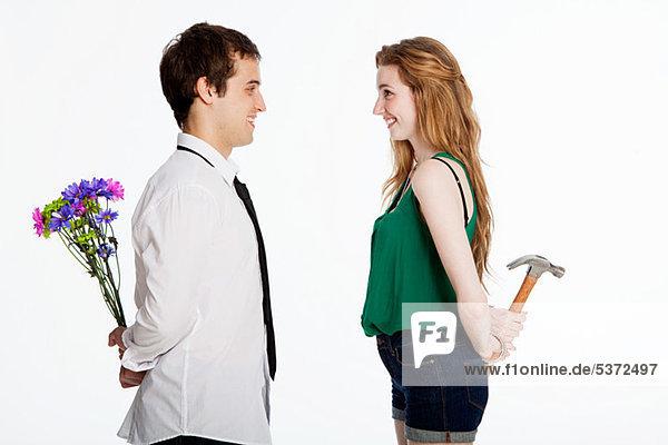 Junges Paar mit Blumen und Hammer auf weißem Grund