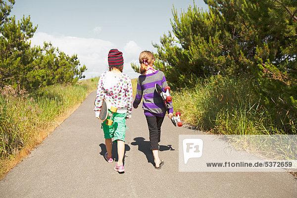 Mädchen mit Skateboards Ländliche Straße