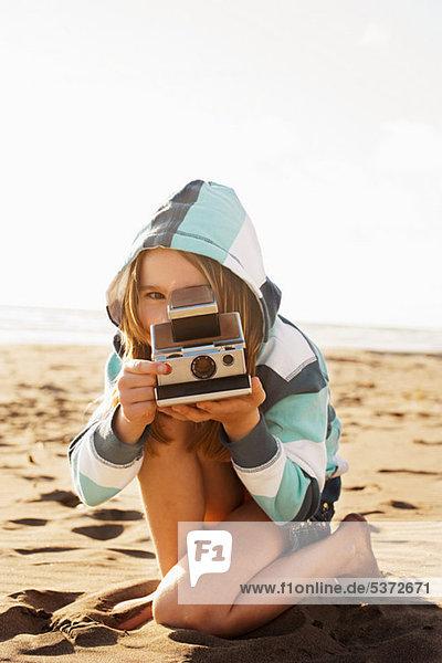 Mädchen mit instant-Kamera am Strand