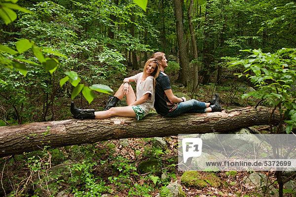 Paar  das sich im Wald gegeneinander lehnt