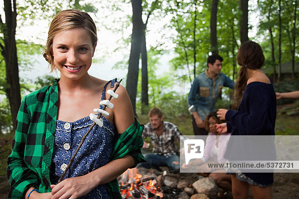Young Woman holding Essen gekocht am Lagerfeuer im Wald