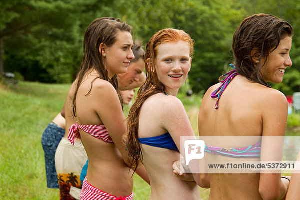 Girls in bikinis watching friends playing around in the country