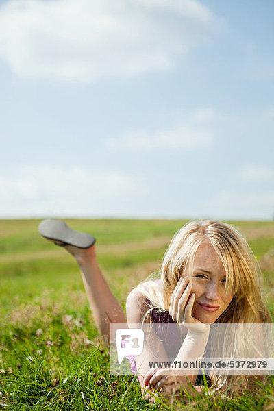 Junge Frau liegen auf ihrer Vorderseite in einem Feld  lächelnd