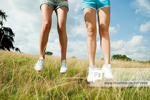 Junge Frauen beim Springen auf einem Feld