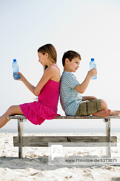 Mädchen und Junge mit Wasserflaschen am Strand