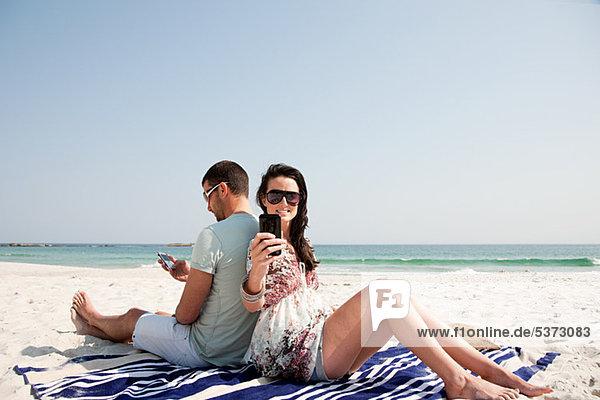 Paar sitzt Rücken an Rücken am Strand und benutzt dabei Mobiltelefone.