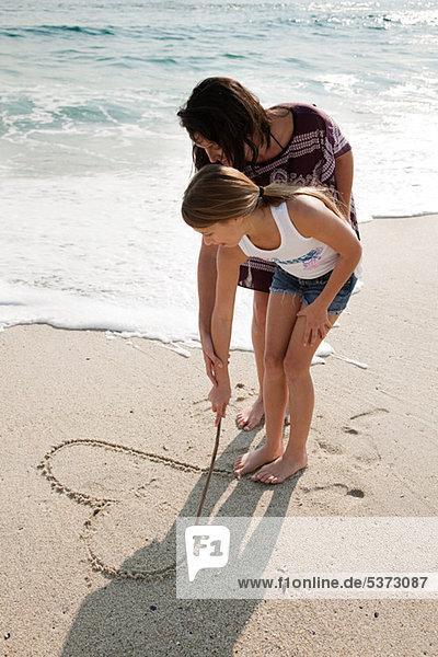 Mädchen ein Herz in den Sand Zeichnung