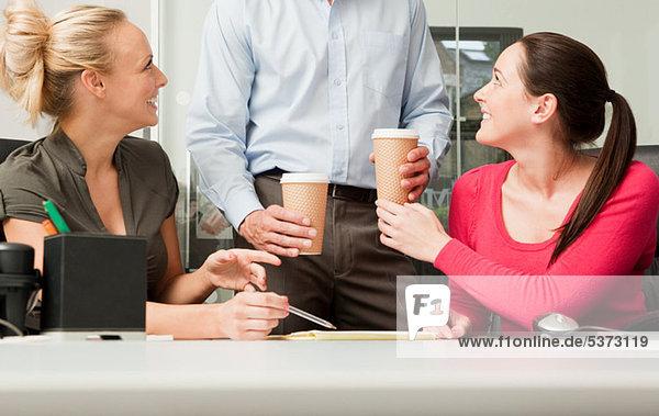 Männlicher Kollege  der weibliche Kollegen Kaffee bringt