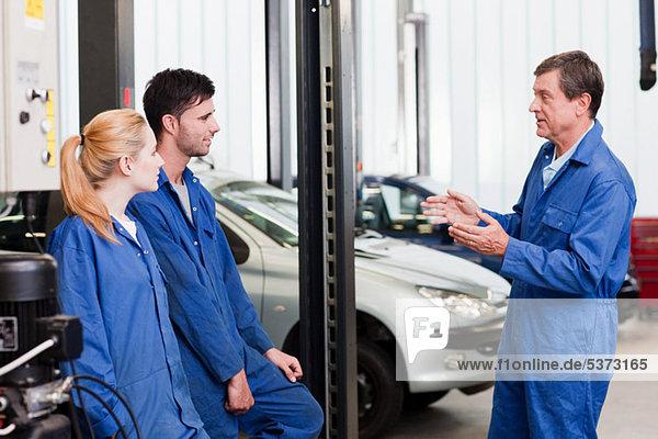 Mechaniker mit Lehrlingen im Gespräch