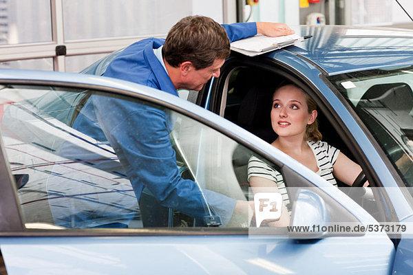 Mechaniker im Gespräch mit Frau im Auto