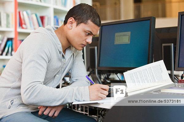Universitätsstudent bei der Arbeit am Computertisch