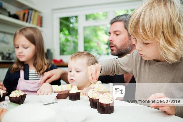 Mittlerer Erwachsener Mann und Familie dekorieren Cupcakes