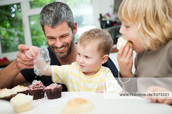Mittlerer Erwachsener Mann  der mit seinen Söhnen Muffins dekoriert.