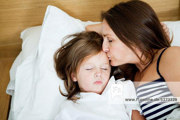 Mittlere erwachsene Frau küsst schlafende Tochter