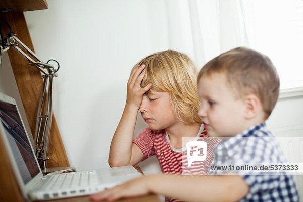 Junge Jungen mit Laptop am Schreibtisch