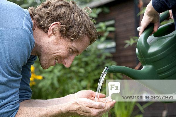 Mann hält Wasser aus Gießkanne.