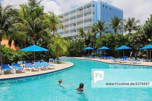 Palme  Niederländische Antillen  Frau  Mann  Regenschirm  Schirm  Hotel  waten  Liege  Liegen  Liegestuhl  Urlaub  gastfreundlich  Schwimmbad  Karibisches Meer  niederländisch  Gast