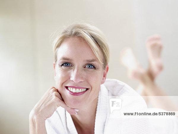 Reife Frau vorne liegend  lächelnd  Portrait