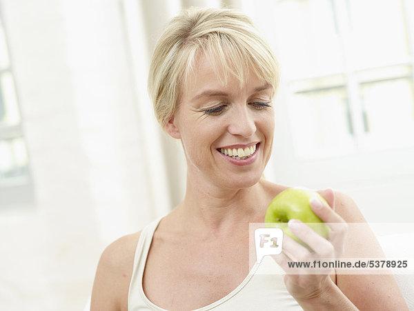 Reife Frau hält Apfel  lächelnd