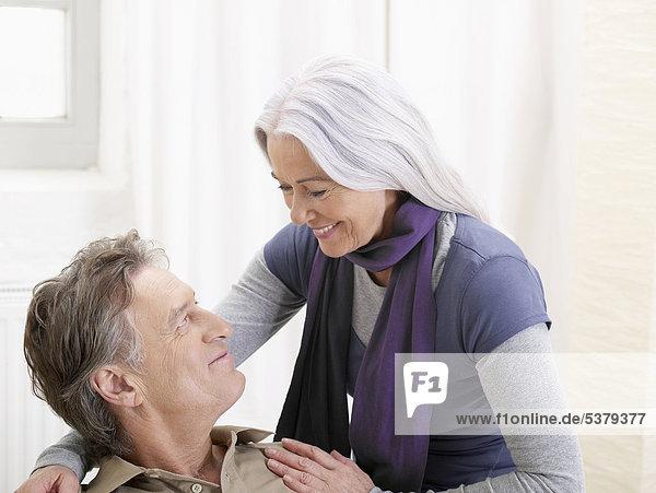 Deutschland  Hamburg  Seniorenpaar schaut sich an  lächelnd