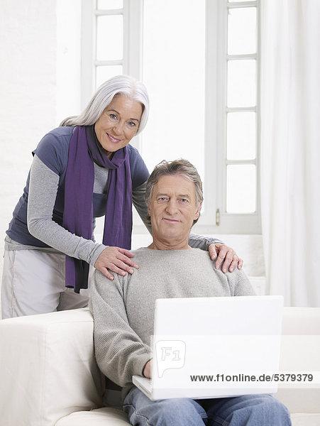 Deutschland  Hamburg  Seniorenpaar mit Laptop  lächelnd  Portrait