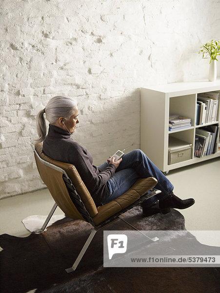Seniorin auf dem Stuhl sitzend und Musik hörend