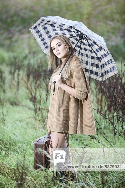 Junge Frau mit Regenschirm und Aktentasche aus Gras