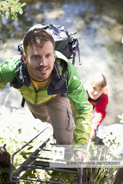 Deutschland  Oberbayern  Paarleiter beim Wandern  lächeln