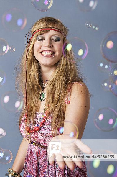 Junge Hippie-Frau mit Blasen auf grauem Hintergrund  lächelnd