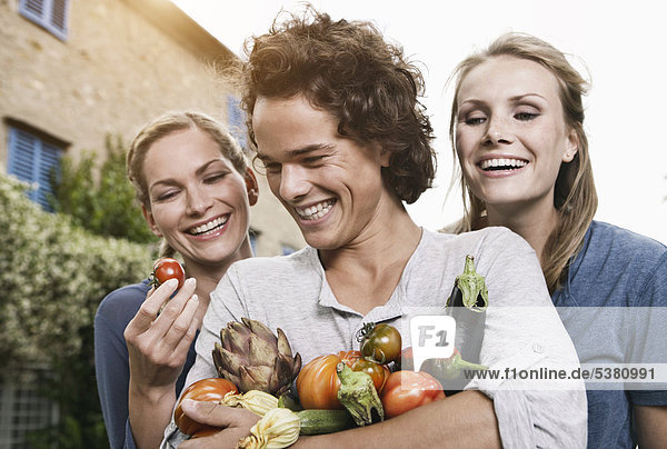 Italy  Tuscany  Magliano  Young man and women holding vegetables  smiling
