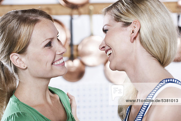 Italy  Tuscany  Magliano  Two young women in kitchen  smiling  close up  portrait