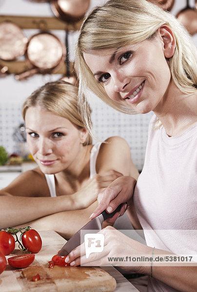 Italien  Toskana  Magliano  Zwei junge Frauen schneiden Tomaten in der Küche  lächelnd