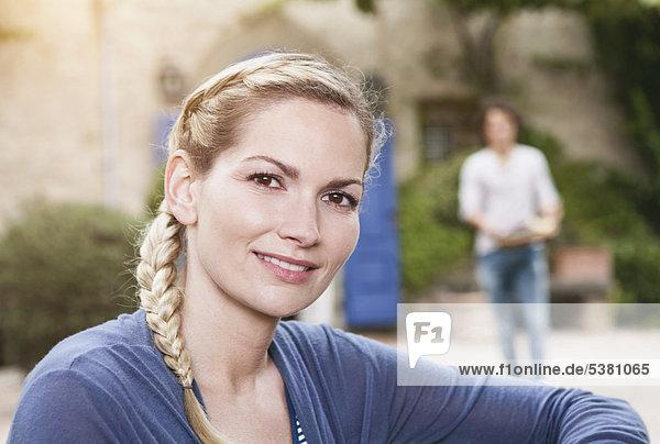 Italien  Toskana  Magliano  Nahaufnahme von junger Frau und Mann im Hintergrund  Lächeln