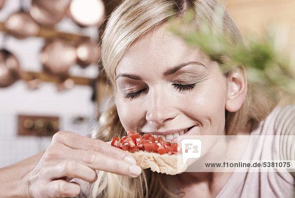 Italien  Toskana  Magliano  Junge Frau riecht Tomaten auf Bruschetta  lächelnd
