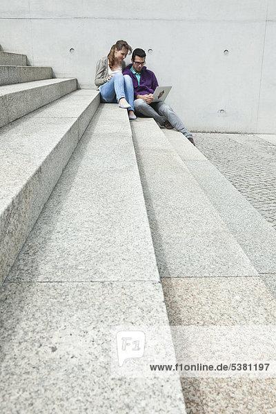 Deutschland  Berlin  Paar mit Laptop im Treppenhaus