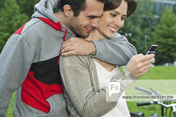 Deutschland  Berlin  Paar mit Handy im Park