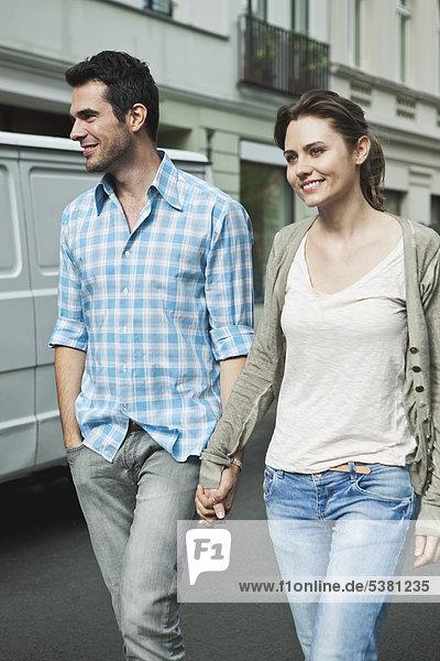 Deutschland  Berlin  Paar geht Hand in Hand durch die Stadtstraße