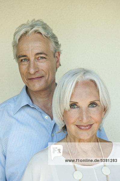 Reifer Mann und ältere Frau vor weißem Hintergrund  Nahaufnahme  lächelnd  Porträt