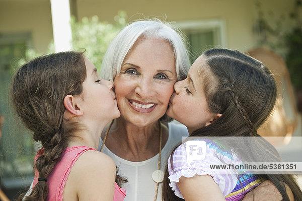 Deutschland  Bayern  Enkelinnen küssen Großmutter  Nahaufnahme