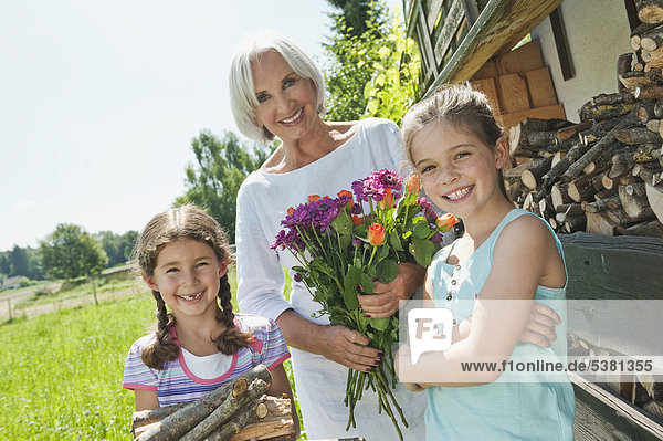 Deutschland  Bayern  Enkelinnen und Großmutter im Garten  lächelnd  Portrait