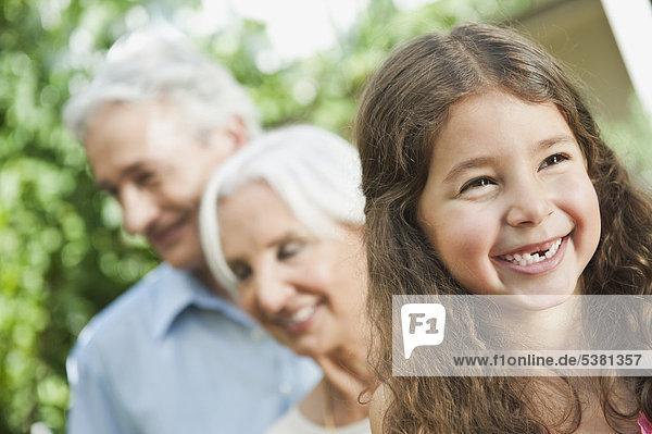 Mädchen lächelt mit Großeltern im Hintergrund