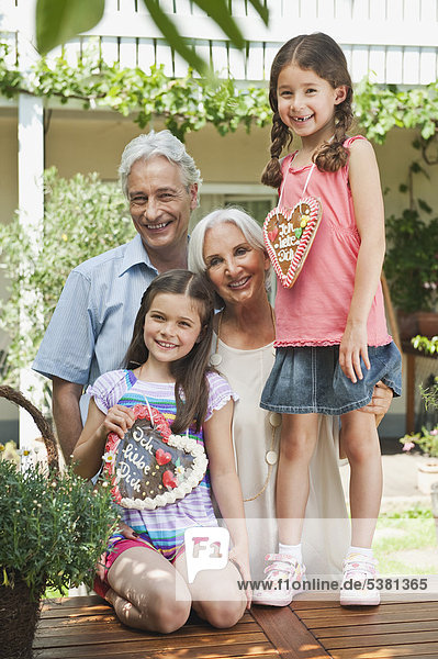 Deutschland  Bayern  Großeltern mit Enkelin  die Lebkuchen hält  lächelnd