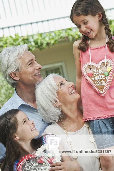 Deutschland,  Bayern,  Großeltern mit Enkelin,  die Lebkuchen hält,  lächelnd