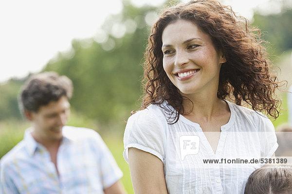 Frau lächelt mit Mann im Hintergrund