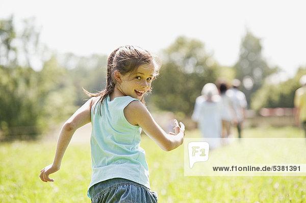 Mädchen läuft mit Familie im Hintergrund