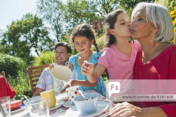 Deutschland  Bayern  Familie bei Kaffee und Kuchen im Garten  lachend