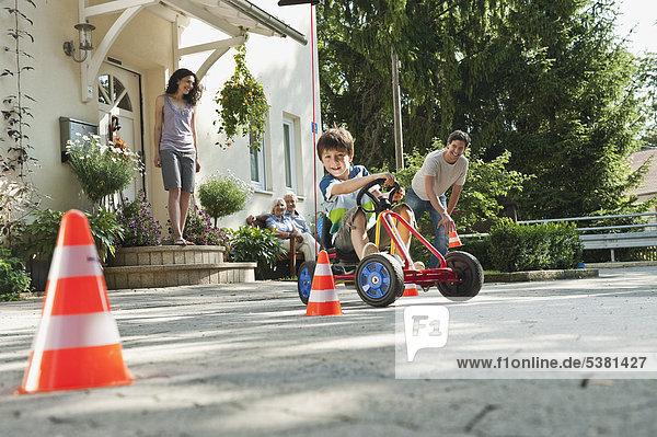 Junge Fahrpedal Go-Kart mit Familie im Hintergrund