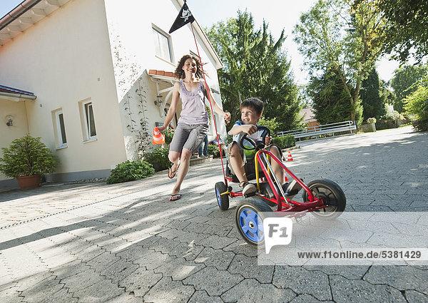 Junge mit Fahrpedal Go-Kart und Frau mit Familie im Hintergrund
