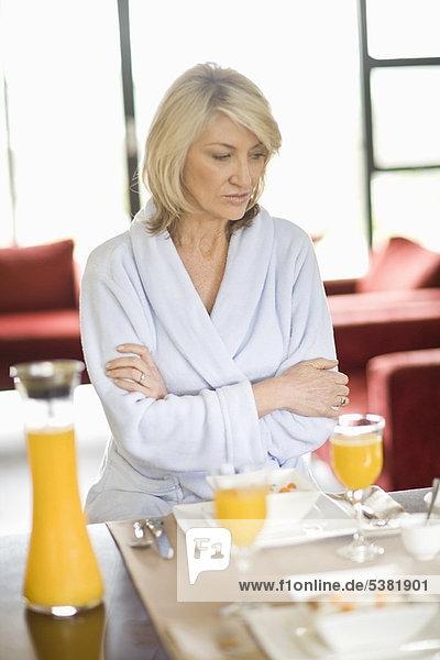 Frau im Bademantel am Frühstückstisch
